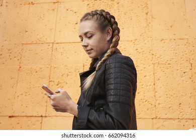 Young attractive hipster female with blond hair reading message on modern mobile phone device and chatting online with friends while standing against the background of the orange wall