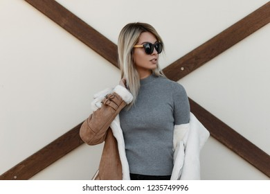 Young attractive hipster girl with black fashionable sunglasses in a gray knitted vintage sweater and jacket with fur posing near a white wall, Autumn trend  style. Fashionable girl