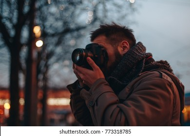 young and attractive hipster man taking photographs with his dslr camera. traveler photographing decorated xmas streets. fashionable clothes, warm jacket and scarf.