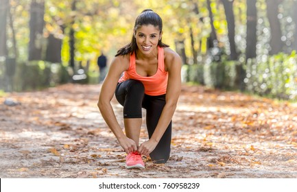 young attractive hispanic attractive 20s woman on sport shoe laces smiling happy and sweet before running workout at amazing beautiful Autumn park forest in fitness and healthy lifestyle concept