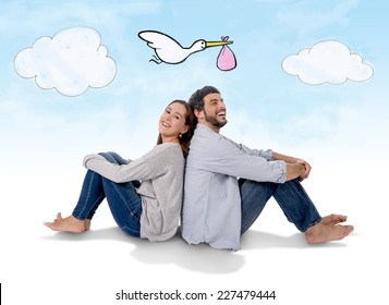 young attractive Hispanic couple on floor, pregnant woman sitting together handsome husband and flying stork bringing baby in pregnancy and family growth concept