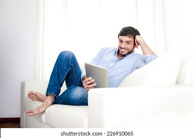 Young attractive Hispanic man at home sitting on white couch using digital tablet or pad looking relaxed smiling at living room enjoying surfing internet watching online movie