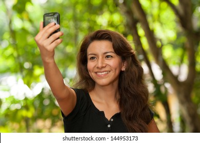 Young attractive Hispanic woman portrait outside green behind taking her own picture