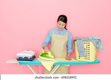 young attractive housewife ironing family clothing isolated on pink background.