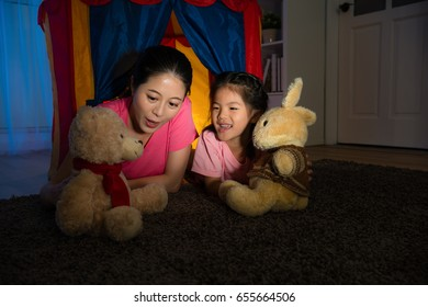 young attractive housewife speaking story for teddy bear toy with smiling beauty kid lying on children tent in living room at night.