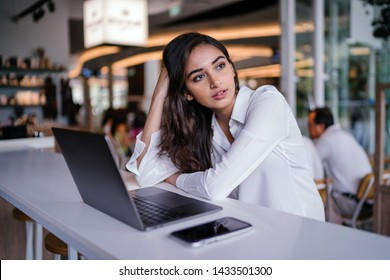 A young and attractive Indian Asian woman looks pensive and concerned as she looks up from her laptop computer. She is planning for her future. She is sitting in a cafe during the day.