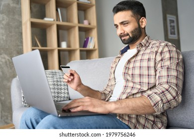 Young attractive indian Hispanic male consumer doing online virtual shopping using laptop and holding credit debit card sitting on sofa at home. Ecommerce and secure financial payments concept.