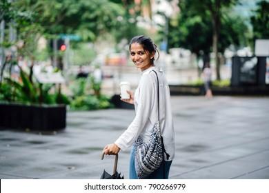 Young and attractive Indian lady walking on grey pavement in a green city with lots of lush, green plants in the background. She is holding an umbrella and a coffee cup with a sling bag.