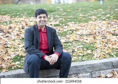 A young attractive Indian man sitting outdoors on a cloudy day in the fall.