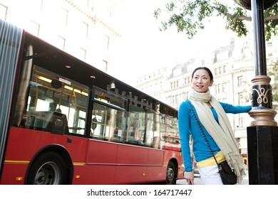 Young and attractive Japanese tourist woman enjoying sightseeing in the destination city of London with red buses and classic buildings around her, during a sunny day on holiday, outdoors.