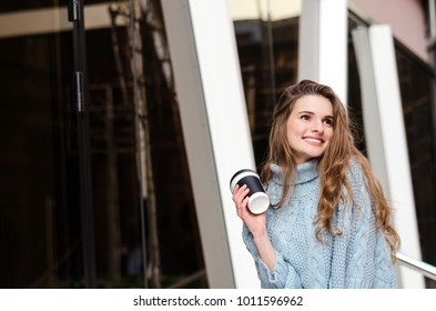 Young attractive lady with long curly hair with coffee to go, wearing stylish clothes