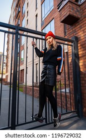 Young attractive lady in red knitting hat stay under  brick house, look at the camers. Smiling beautiful hipster happy woman in city street, wearing stylish clothes. Autumn trend, urban stydent style