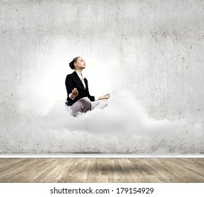 Young attractive lady sitting on cloud and practicing yoga
