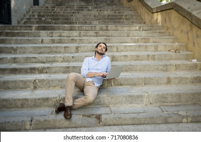 young attractive latin man sitting on city staircase working with laptop computer looking satisfied and confident thoughtful and pensive in new business technology and lifestyle concept