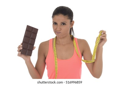 young attractive latin woman in fitness top holding taylor measure tape and chocolate bar in healthy nutrition to keep diet versus tasty and high content calories food isolated in white background