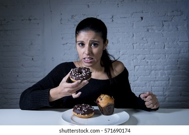 young attractive latin woman sitting at table feeling guilty forgetting diet eating dish full of junk sugary unhealthy food such as chocolate donut and muffin cake in sugar addiction