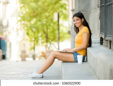 young attractive latin woman in trendy casual clothes studying or working on laptop computer in european city urban background