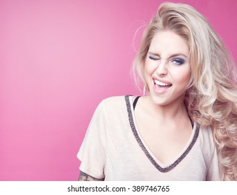 Young attractive laughing winking blonde happy woman expressive portrait beauty concept