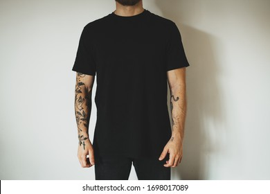 young attractive male hipster with a beard and tattoos, dressed in a black blank t-shirt, posing on a white wall background. Empty space for you logo or design.