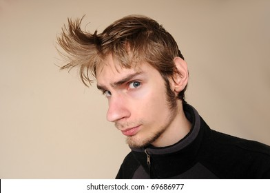 A young attractive young male looking at you with a unique hairstyle.