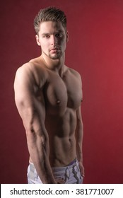 Young attractive male model against a red background. Handsome undressed man looking into camera. Sexy shirtless and muscular guy.