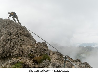 young attractive male mountain climber on a steep and exposed Via Ferrata in Alta Badia in the South Tyrol in the Italian Dolomites