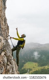 young attractive male mountain climber on a steep and exposed Via Ferrata in Alta Badia in the South Tyrol in the Italian Dolomites pointing to the summit