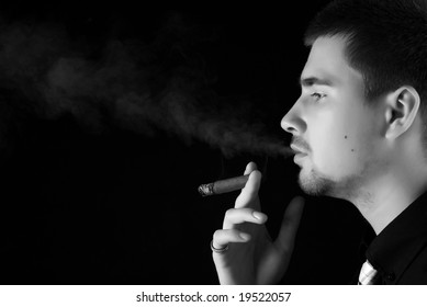young attractive man in a black suit with cigar