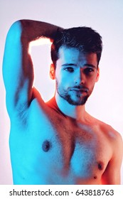 Young, attractive man in blue and red lighting with white background