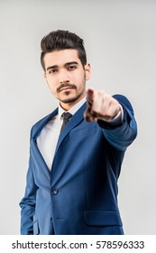 Young attractive man in a blue suit showing a finger forward on a gray background. Isolated
