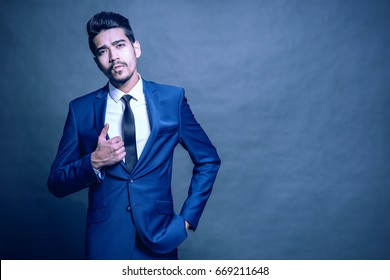 Young attractive man in a blue suit on a blue background. Toned
