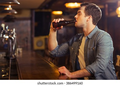 Young attractive man in casual clothes is drinking beer while sitting at bar counter in pub