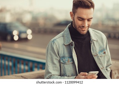 Young attractive man in casual wear using his cell phone, walking through an urban area of a city