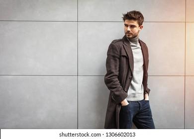 junger attraktiver Mann im Mantel, der auf einer grauen Wand posiert, stylischer Mann