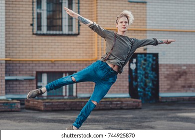 Young attractive man dancing in urban background. the dancer dances on the street. jump view