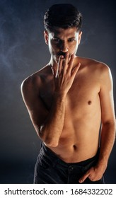 Young attractive man dressed in black jeans smoking a cigarette