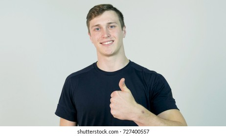 Young attractive man dressed in black t-shirt standing over white background looking at camera and showing thumb up gesture