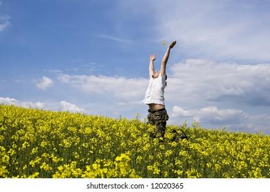 Young attractive man enjoying summer field