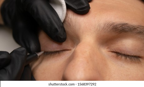 Young attractive man eye close-up with the master hand in black gloves and permanent makeup machine with a needle. Male permanent makeup procedure.