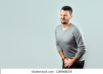 A young, attractive man feels pain in his groin, arms folded between his legs. Experiencing pain, male problems, potency.