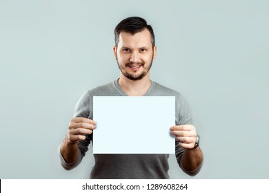 A young, attractive man holding a blank white A4 sheet, on a light background. mockup, layout, copy space.