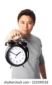 Young attractive man holding a clock. Wearing a grey shirt. White background.