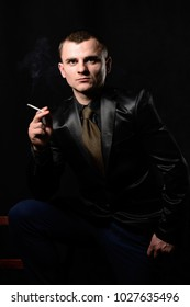 Young attractive man holds a cigarette in a suit and tie on a black background.
