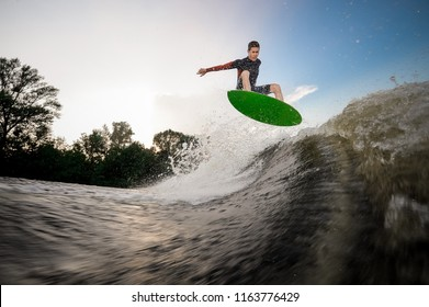 Young attractive man jumping on the green wakeboard on high wave of motorboat on the background of trees