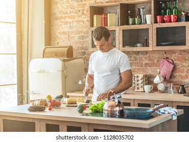 young attractive man in the kitchen cuts a baguette
