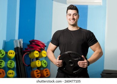 Young attractive man lifting weights at gym room