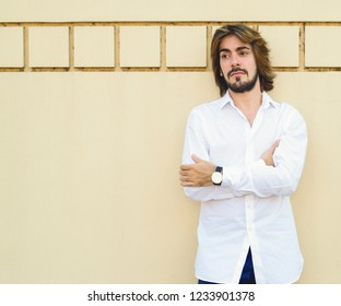 Young attractive man with long hair and beard, dressed in white shirt is leaning on the yellow wall and looks to one side in profile. Fashion