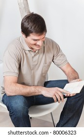 Young attractive man looking at color guide and smiling