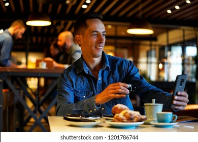 Young attractive man looking at his mobile phone while having breakfast at a sitting table