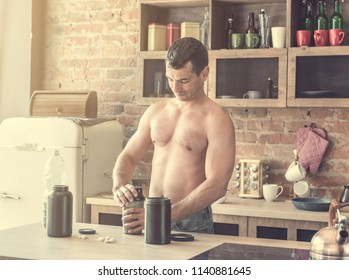 Young attractive man makes a protein cocktail in the kitchen